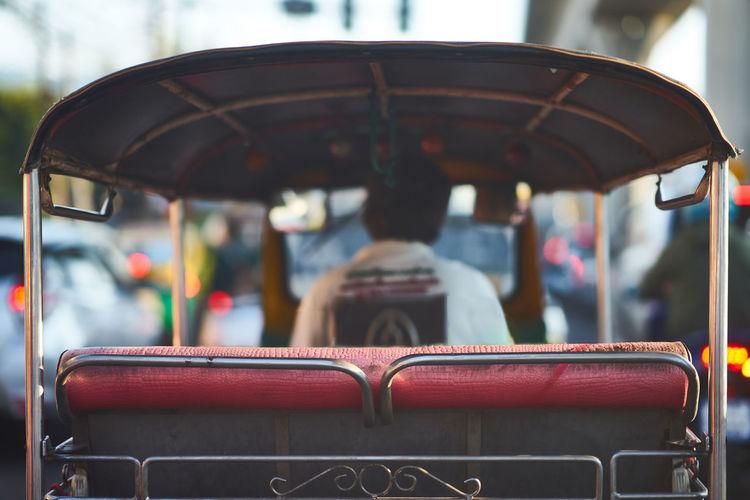 Tuk tuk or thai three wheels vehicle on blur background in rear aspect