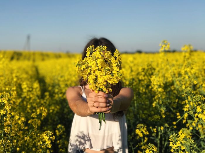 Woman holding yellow flowers in field