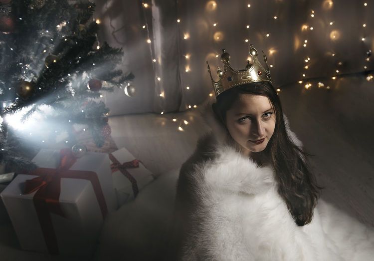 Portrait of woman with illuminated christmas lights during winter
