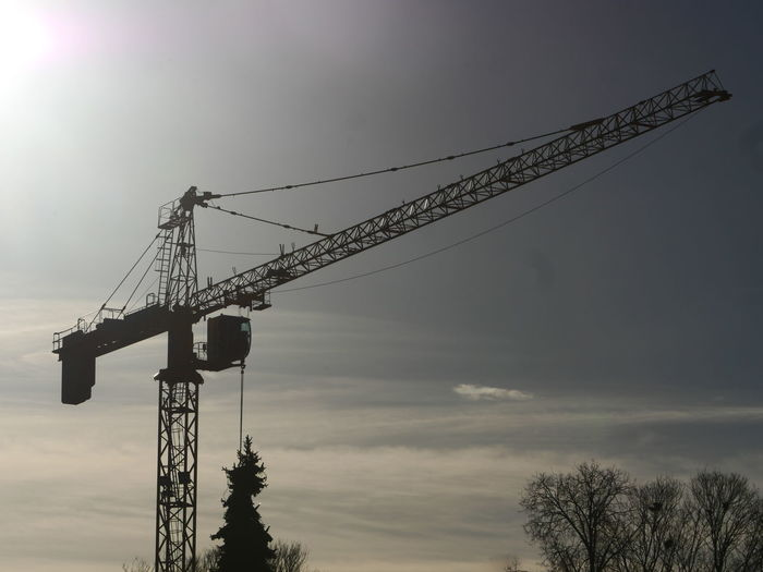 Low angle view of crane against sky during sunset