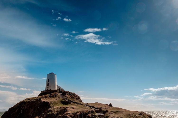 Low angle view of lighthouse on mountain against blue sky