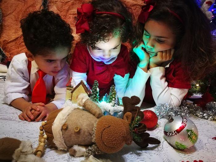 Siblings Looking At Christmas Decoration