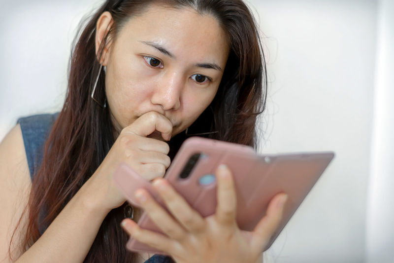 Portrait of young woman using mobile phone at home