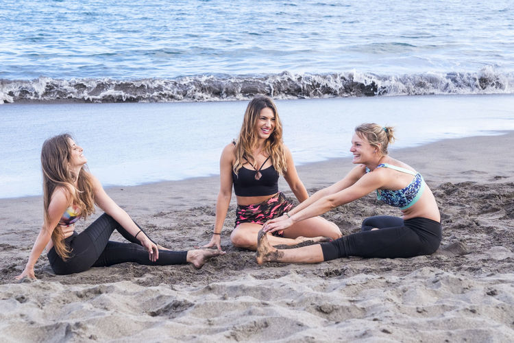 Smiling friends exercising while sitting at beach