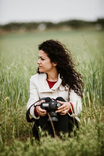 Beautiful woman with camera sitting on field