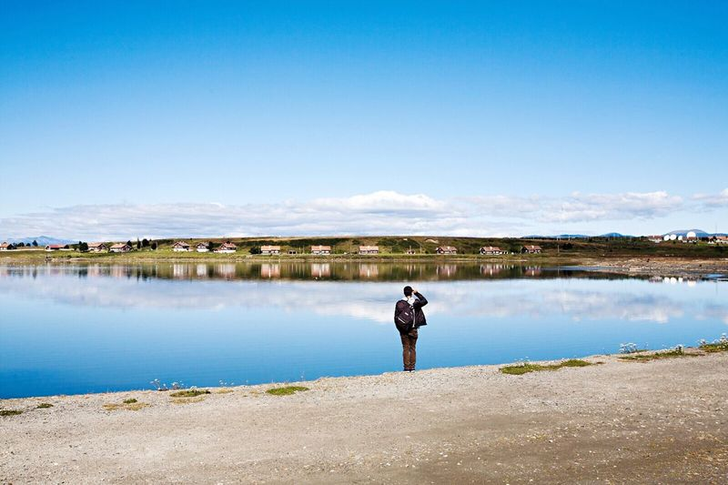 Man standing at calm lake