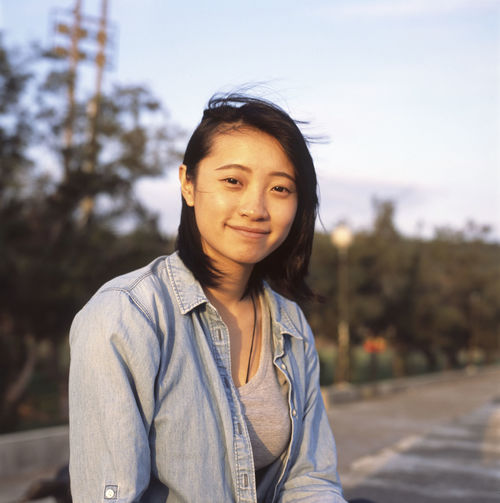Portrait of smiling young woman against sky during sunset