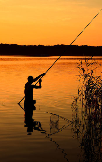 Fisherman with fishing rod in lake water at sunset Calm Evening Fisherman Fishing Fishing Rod Fishing Time Hobbies Idyllic Lake Lake View Leisure Activity Lifestyles Man Nature Orange Color Outdoors River Scenics Silhouette Sky Sunset Tranquil Scene Tranquility Water People And Places Love Yourself Summer Exploratorium
