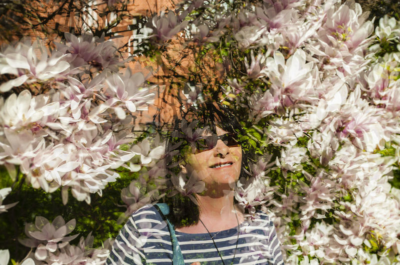 Multiple Exposure Of Smiling Mid Adult Woman And Flowers During Springtime