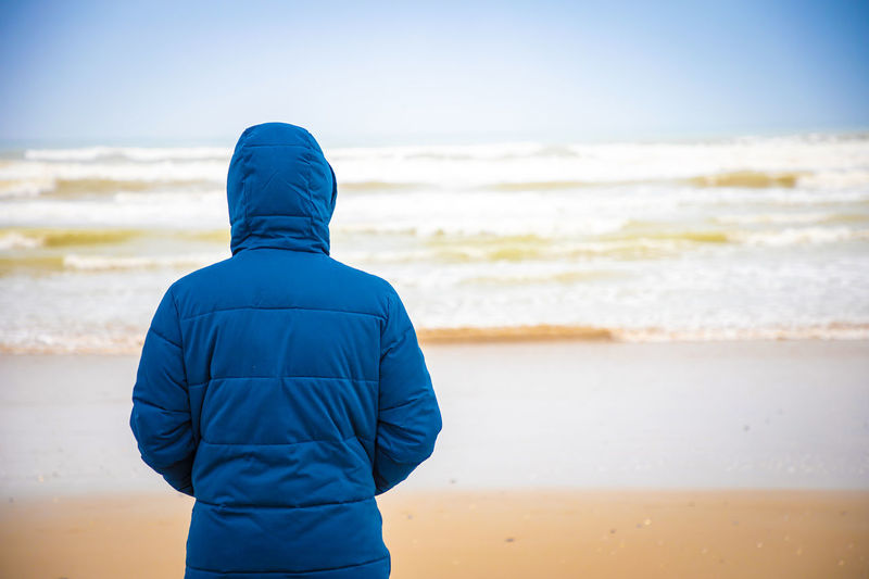 Rear View Land Beach Sea Blue Water One Person Hood Leisure Activity Clothing Nature Motion Hooded Shirt Lifestyles Hood - Clothing Sky Focus On Foreground Real People
