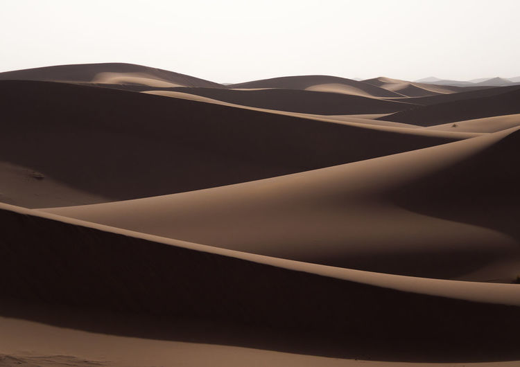 Close-up of sand dune against clear sky