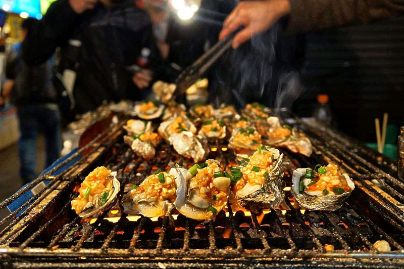 Cropped hand preparing seafood on barbecue grill at market