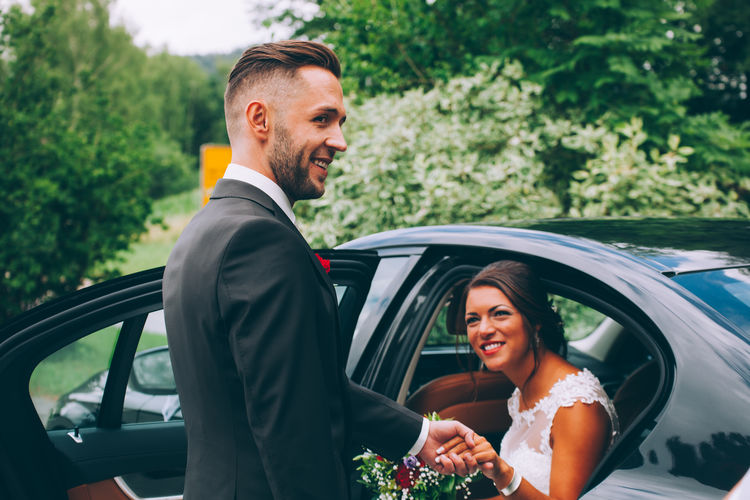 Bride Holding Hands Of Groom While Sitting In Car