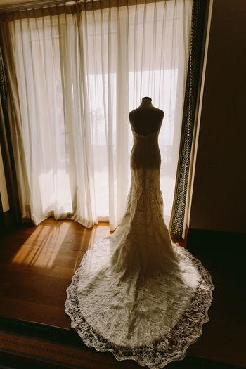 Wedding dress against curtain