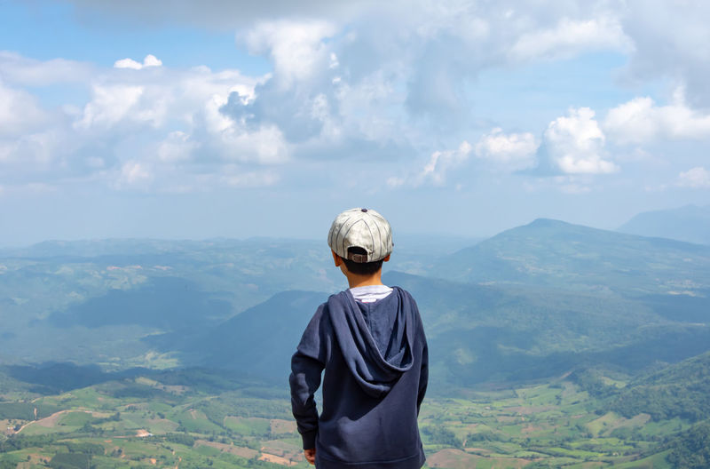 Rear view of boy standing against mountains and sky