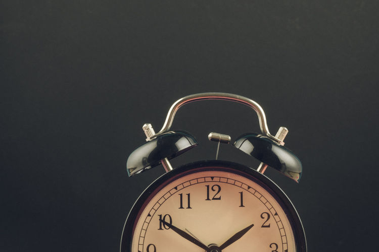 alarm clock on dark background Clock Time Alarm Clock Copy Space Indoors  No People Number Night Low Angle View Close-up Accuracy Bell Studio Shot Still Life Clock Face Communication Minute Hand Retro Styled Black Background