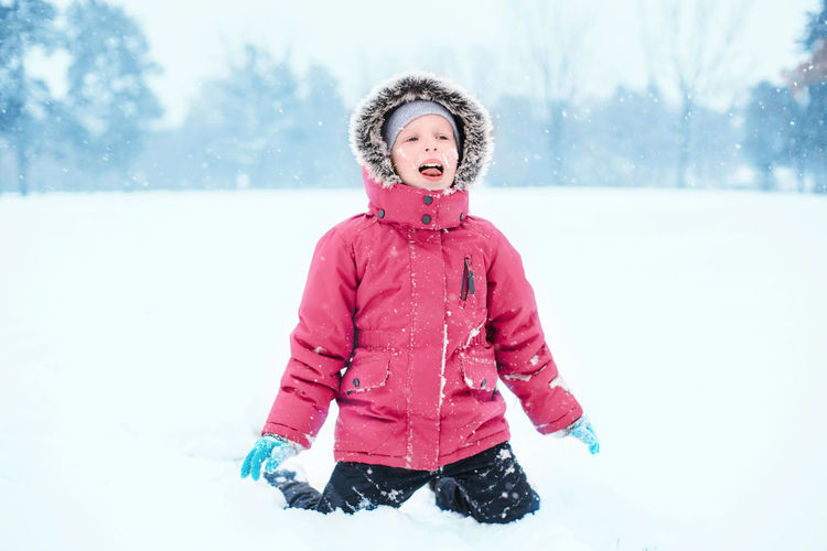 Caucasian excited girl child eating licking snow during cold winter snowy day. kids outdoor