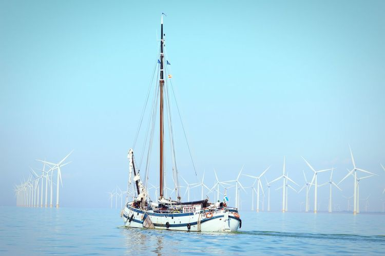 Sailboat with wind turbines in sea against clear sky