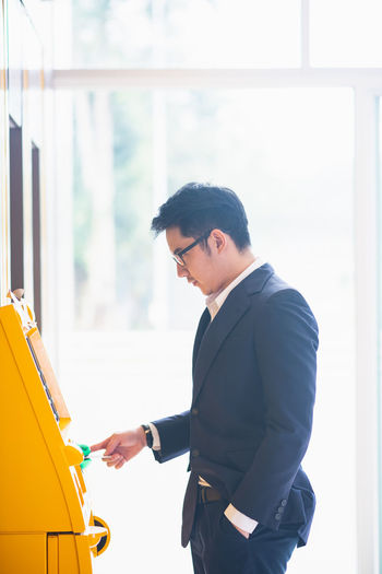 Side View Of Young Businessman Using Atm
