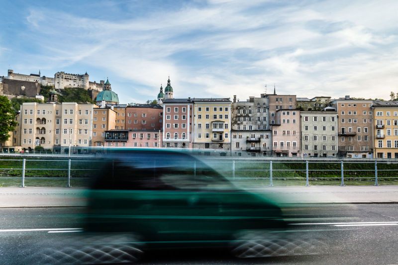 Motion blur of car with buildings in background