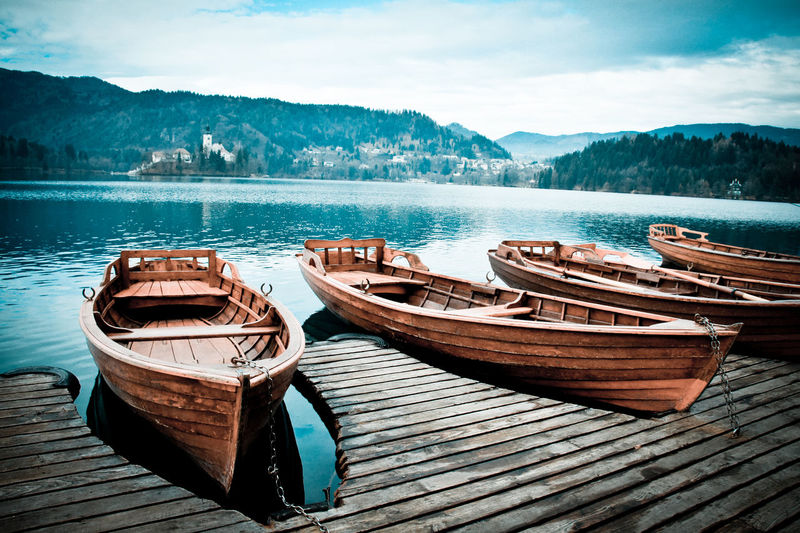 Boats Moored On Lake Against Sky