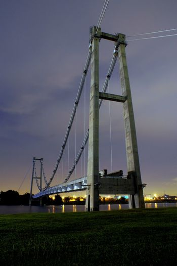 Low angle view of illuminated bridge against sky at sunset