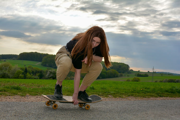 A young girl squats skateboarding on a road in green nature