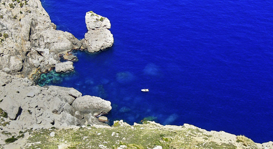 A white sail boat in a rocky bay on the Spanish island of Majorca in a wonderfully dark blue water. Bay Area Majorca SPAIN Baleares Bay Beauty In Nature Blue Boat Dangerous Dark Blue Day High Angle View Nature No People Ocean Outdoors Riff Rock - Object Rocks Rocks Under Water Sailing Sailng Boat Scenics Sea Water