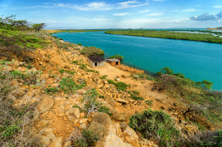 Dry coast next to beautiful blue Caribbean Sea in La Guajira, Colombia Beach Blue Caribbean Colombia Green Guajira Idyllic La Guajira La Guajira Colombia Landscape Natural Nature Punta Gallinas Sand Sea Seascape Season  Sky Summer Sunlight Sunshine Tranquil Tropical View Water