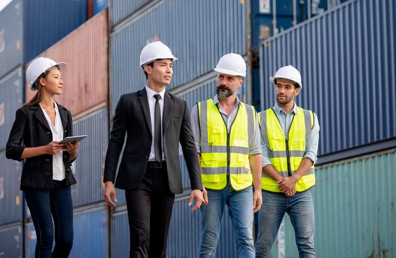 Men standing in front of people looking away