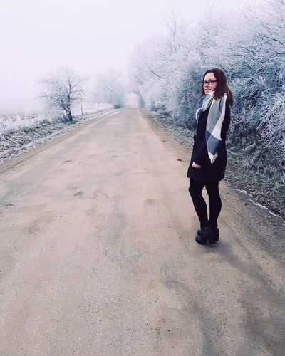 Portrait of woman standing on road during winter