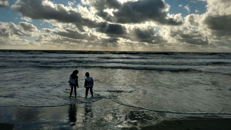 Rear View Of Friends Standing On Shore At Beach Against Cloudy Sky