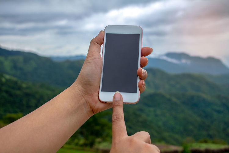 Cropped image of hand holding smart phone against mountain