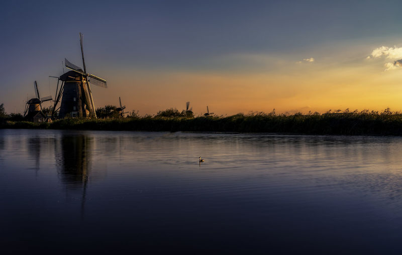 Scenic View Of Lake By Traditional Windmill Against Sky During Sunset