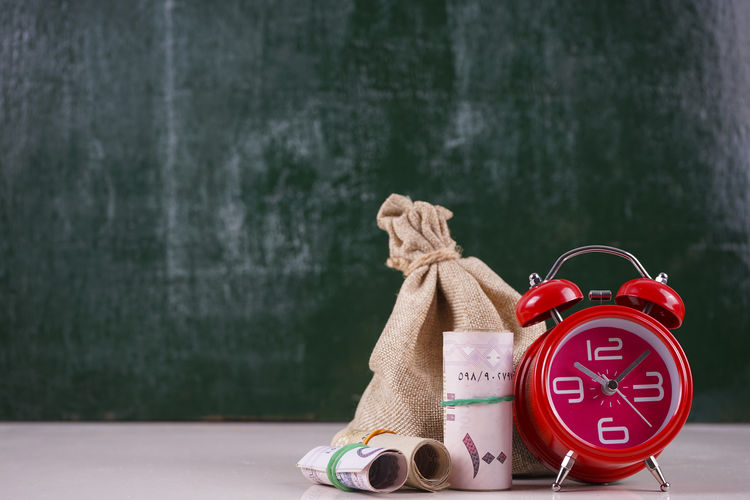 Close-up of alarm clock with paper currencies and burlap on table against blackboard
