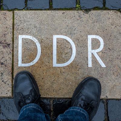 Floortrait with symbol Black Color Blick Nach Unten Canvas Shoe Close-up Day DDR Floortraits Foot Shot Footwear Fussboden Fußbild Information Lifestyles Look Down Outdoors Pair Part Of Personal Perspective Perspective Standing Standpunkt