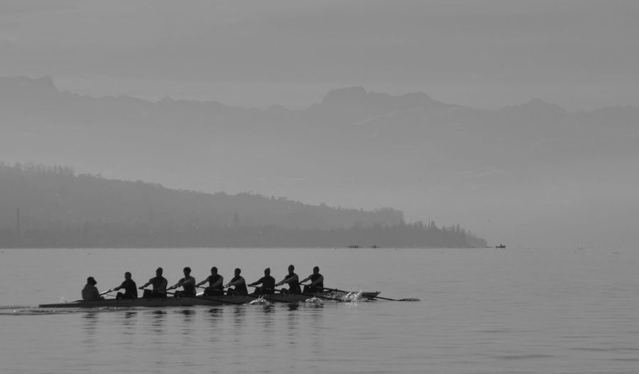 Rowing team in scull on lake during foggy weather