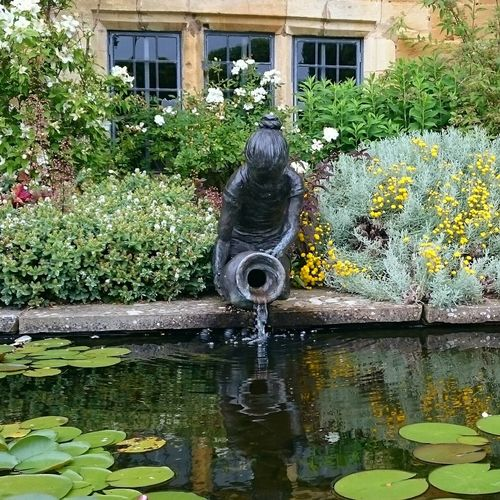 Water Fountain Building Exterior Architecture Built Structure Drinking Fountain Outdoors Day Motion No People Spraying Nature Puddle Water Pipe Flower Tranquility Cotswolds Eeyem Photography Beauty In Nature Flowers,Plants & Garden Plant Reflection_collection Reflections In The Water Tranquillity