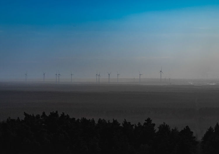 Wind Turbines On Landscape Against Sky