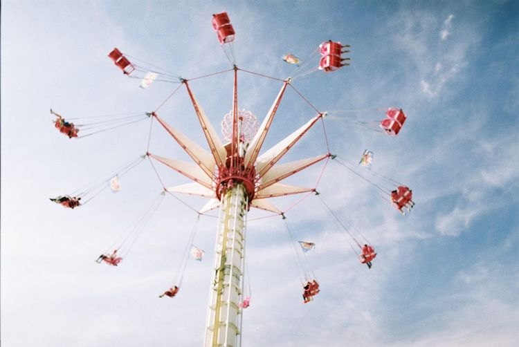 Low angle view of chain swing ride at amusement park ride against sky