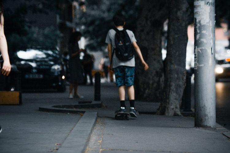 Rear view of people walking on sidewalk in city