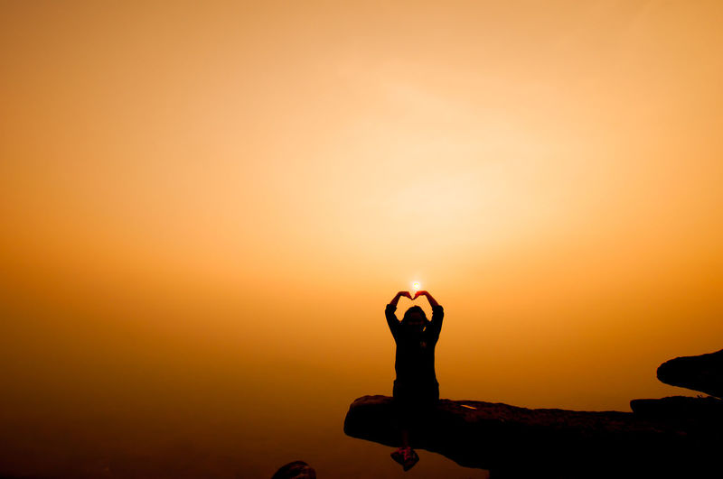 Silhouette person making heart shape on cliff against sky during sunset