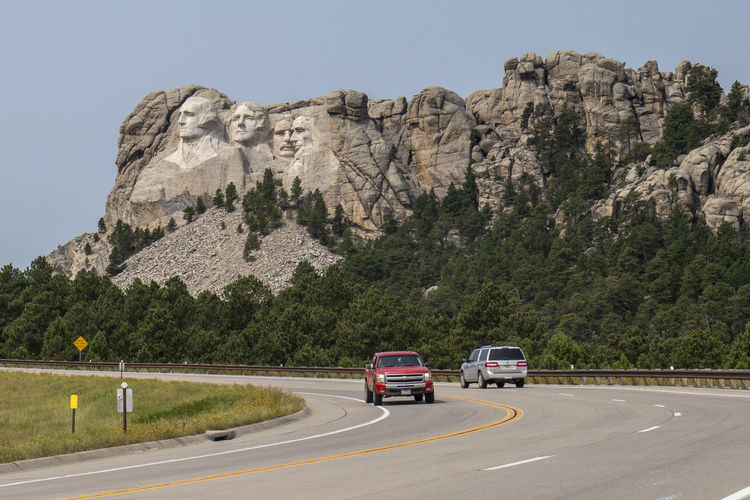 Mount Rushmore Mount Rushmore National Memorial Car Day Formation Land Vehicle Mode Of Transportation Motion Motor Vehicle Mountain Mountain Range Nature No People on the move Outdoors Plant Road Rock Rock - Object Rock Formation Sky Solid Transportation Travel Tree