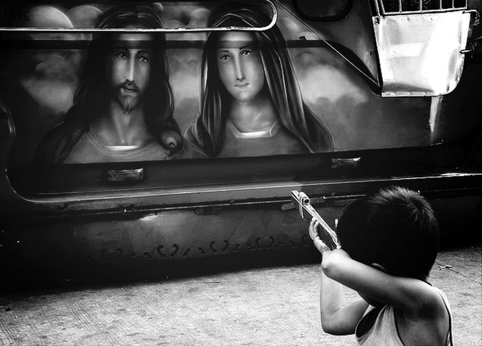 Boy Aiming With Toy Gun At Graffiti Of Jesus Christ And Virgin Mary