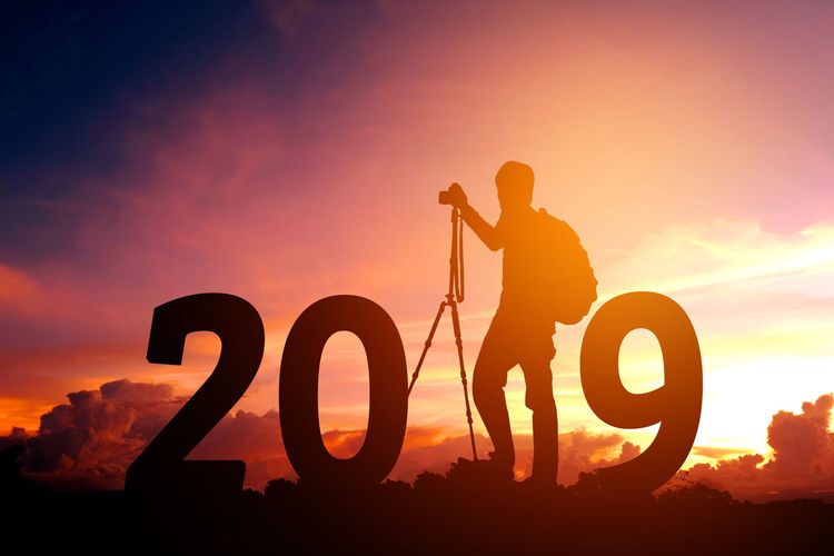 2019 Happy New Year! Beauty In Nature Cloud - Sky Communication Dollar Sign Full Length Happy New Year Happy New Year 2019 Land Leisure Activity Lens Flare Lifestyles Men Nature One Person Orange Color Outdoors Real People Silhouette Sky Standing Sun Sunlight Sunset Text