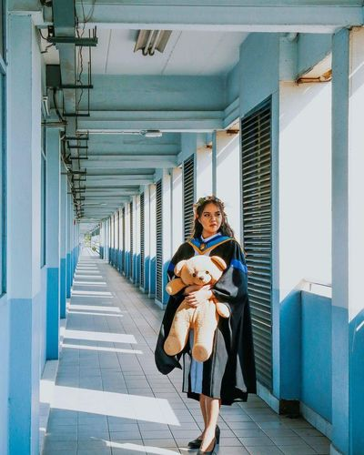 Woman in graduation gown holding teddy bear while standing in corridor