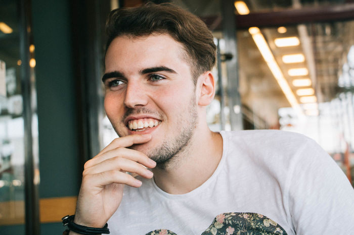Boy Casual Casual Clothing Close-up Coffee Shop Coffee Shop Scene Day Focus On Foreground Front View Hand On Chin Headshot Leisure Activity Lifestyles Man People Together Person Portrait Selective Focus Smiling