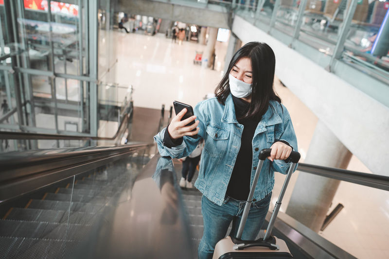 Woman wearing flu mask standing on escalator holding smart phone at mall