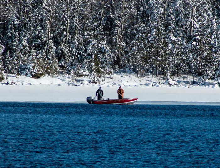 TWO FISHERMAN ON BOAT IN WINTER