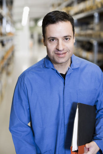 Portrait of smiling man standing in factory